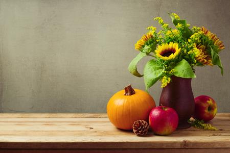 Decorazione tavola di festa del ringraziamento con girasoli, zucca e mele