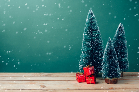 cajas navideñas: Christmas gift boxes under pine tree on wooden table over green background