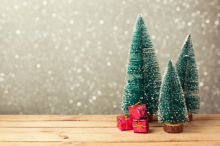 Christmas gift boxes under pine tree on wooden table over bokeh background Stockfoto