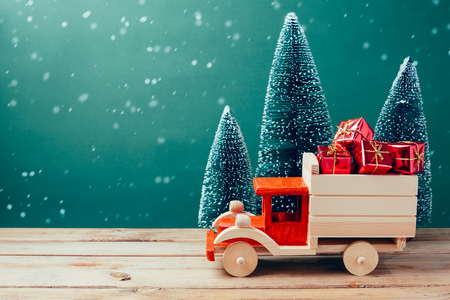 Christmas toy truck with gift boxes and pine tree on wooden table over green background Stockfoto