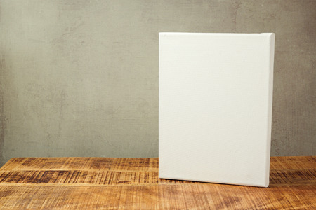 white canvas: White canvas on wooden table over rustic background. Mock up template Stock Photo