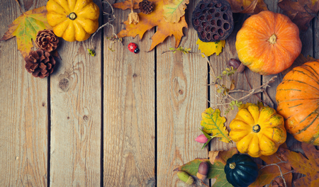 Thanksgiving dinner background. Autumn pumpkin and fall leaves on wooden table. View from above Stock Photo