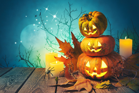 Halloween background with pumpkin jack o lantern on wooden table over spooky trees