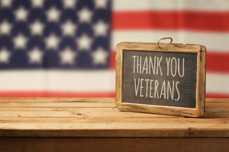 재향 군인의 날 배경으로 나무 테이블과 미국 국기에 칠판