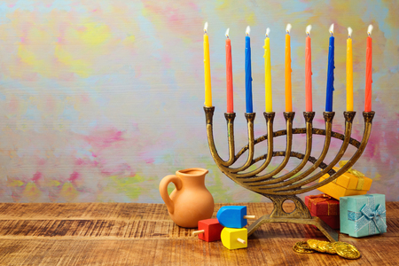 Jewish holiday Hanukkah celebration with menorah, dreidel, gifts and oil jug on wooden table