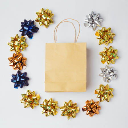 christmas shopping bag: Christmas shopping bag with bows and stars on white background. Flat lay. Stock Photo