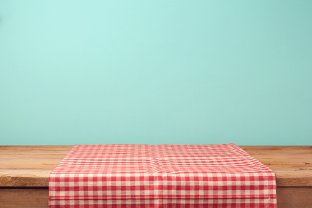 RED WALLPAPER: Empty wooden deck table and red checked tablecloth over mint wallpaper background