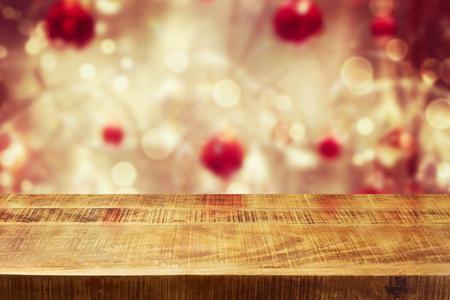 Fondo de vacaciones de Navidad con mesa de madera vacía de la mesa durante bokeh de invierno. Listo para el montaje del producto