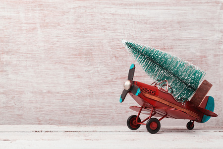Christmas background with rustic vintage airplane toy and pine tree Standard-Bild