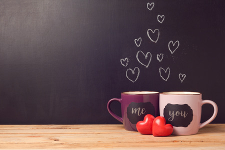 Valentine's day concept with hearts and cups over chalkboard background Banque d'images