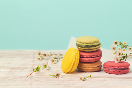 love life: Macarons with flowers over mint background Stock Photo