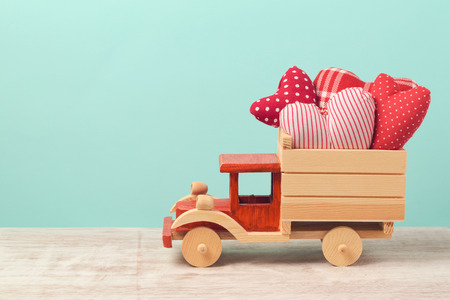 toy truck: Valentines day holiday concept with toy truck and heart shapes over mint background