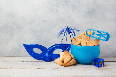 Jewish holiday Purim concept with hamantaschen cookies or hamans ears and carnival mask over rustic background