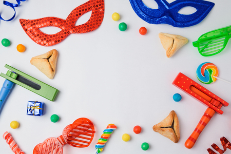 Jewish holiday Purim concept with hamantaschen cookies, carnival mask and noisemaker on white background. View from above