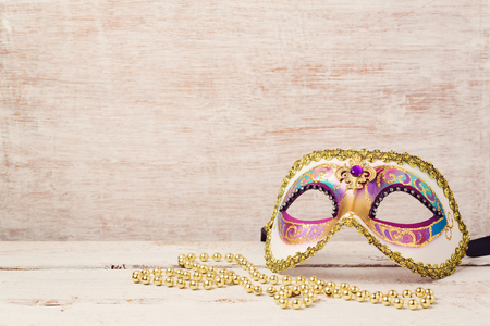 Mardi gras mask and beads for party on wooden background