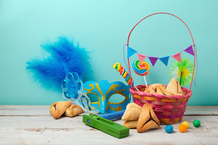 haman: Jewish holiday Purim concept with hamantaschen cookies or hamans ears and carnival mask over blue background