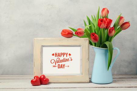 Valentijnsdag concept met tulpen bloemen en fotolijst over rustieke achtergrond Stockfoto