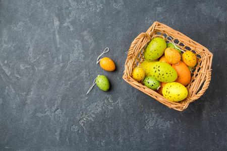 decoracion mesas: concepto de vacaciones de Pascua con la decoración de huevos en la cesta sobre fondo pizarra. Vista desde arriba
