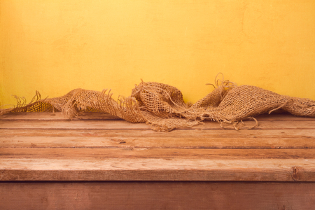 sackcloth: Empty wooden deck table and sackcloth over yellow wall background for product montage display