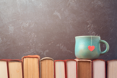 libros antiguos: Valentines day concept with tea cup on books over blackboard background