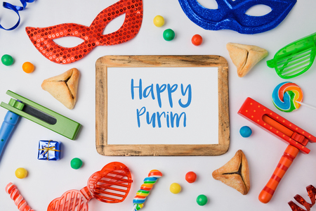haman: Jewish holiday Purim concept with hamantaschen cookies, carnival mask and photo frame on white background. View from above