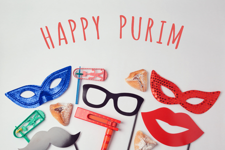 holiday tradition: Purim celebration concept with carnival mask and photo props on white background. Top view from above Stock Photo