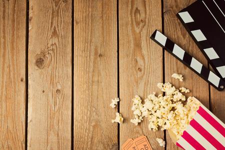 映画クラッパー ボードと木製の背景にポップコーン。上から平面図 写真素材