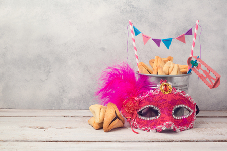 Purim holiday concept with hamantaschen cookies or hamans ears in bucket and carnival mask over rustic background Stock Photo