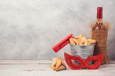 소박한 배경 hamantaschen 쿠키 또는 hamans 귀, 카니발 마스크와 와인 병 유대인 휴일 Purim 개념