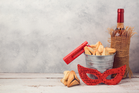Jewish holiday Purim concept with hamantaschen cookies or hamans ears, carnival mask and wine bottle over rustic background