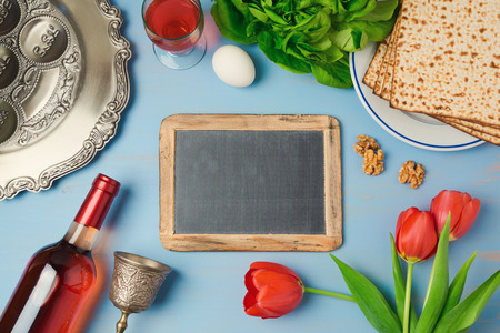 matzoh: Passover holiday concept with chalkboard, seder plate and matzoh on wooden background. Top view from above Stock Photo