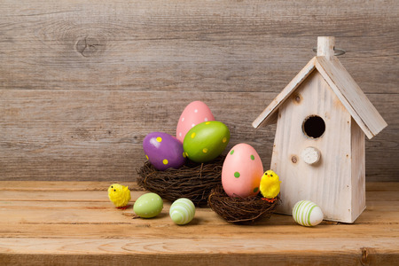 holiday house: Easter holiday concept with eggs decoration, bird house and nest over wooden background Stock Photo
