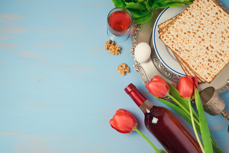 Passover holiday concept seder plate, matzoh and tulip flowers on wooden background. Top view from above