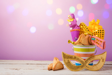 Purim holiday concept with carnival mask and gifts over bokeh lights background Stock Photo