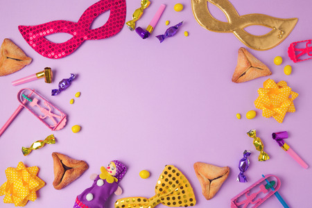 Purim holiday concept with carnival mask, hamans ears cookies and party supplies on purple background. Top view from above with copy space Stok Fotoğraf