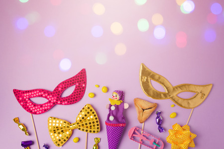 Purim holiday concept with carnival mask and party supplies on purple background with bokeh lights. Top view from above with copy space Stockfoto