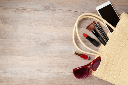 sun glasses: Woman bag with makeup and fashion objects on wooden table. Top view from above Stock Photo