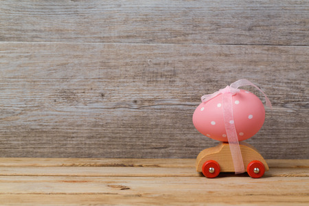 Easter holiday concept with egg on toy car over wooden background