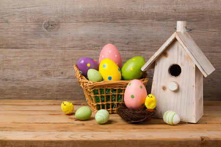 holiday house: Easter holiday concept with eggs basket and bird house over wooden background