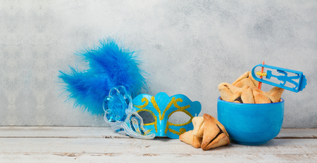 holiday tradition: Jewish carnival Purim celebration concept with hamantaschen cookies and mask over rustic background