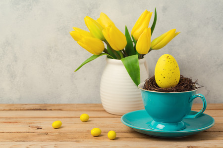 Easter holiday concept with egg in coffee cup and tulip flowers on wooden table
