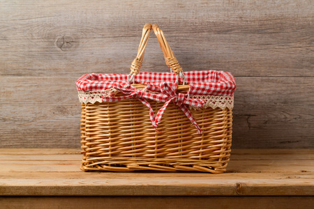 Picnic basket with checked cloth on table over wooden wall background Stock Photo