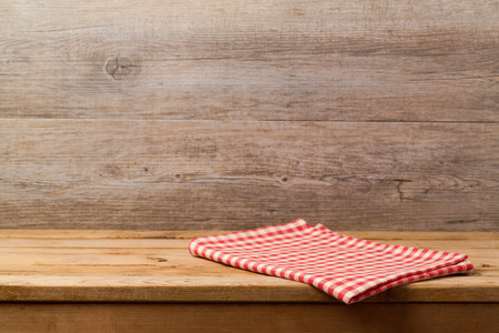 Empty wooden deck table with checked red tablecloth over wooden wall background for product montage display