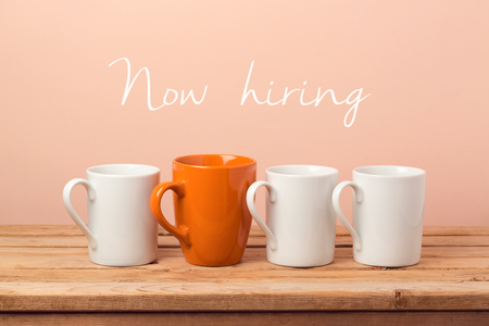 Job recruit concept with coffee cups and text Now hiring. Business background