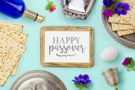 matzoh: Passover holiday concept with wine bottle, matzoh and photo frame over mint background. Top view from above