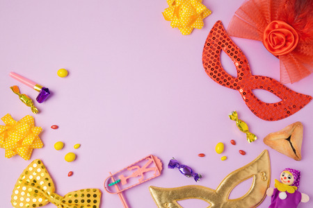 hamantaschen: Purim holiday concept with carnival mask and party supplies on purple background. Top view from above. Flat lay Stock Photo