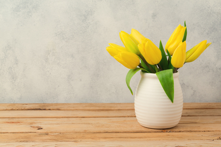 bouquet fleur: Tulip flower bouquet on wooden table over rustic background. Spring season concept