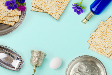 matzoh: Passover holiday concept with wine bottle, matzoh and spring flowers over mint background with copy space. Top view from above