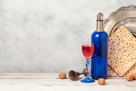 Passover holiday concept with blue wine bottle and matzoh over rustic background with copy space Foto de archivo
