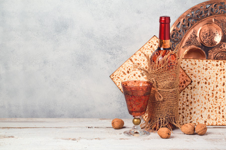 Passover holiday concept with wine and matzoh over rustic background with copy space
